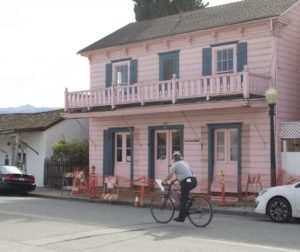 A cyclist rides past La Casa Rosa in San Juan Bautista, where the sidewalk is blocked. Photo by Noe Magaña.