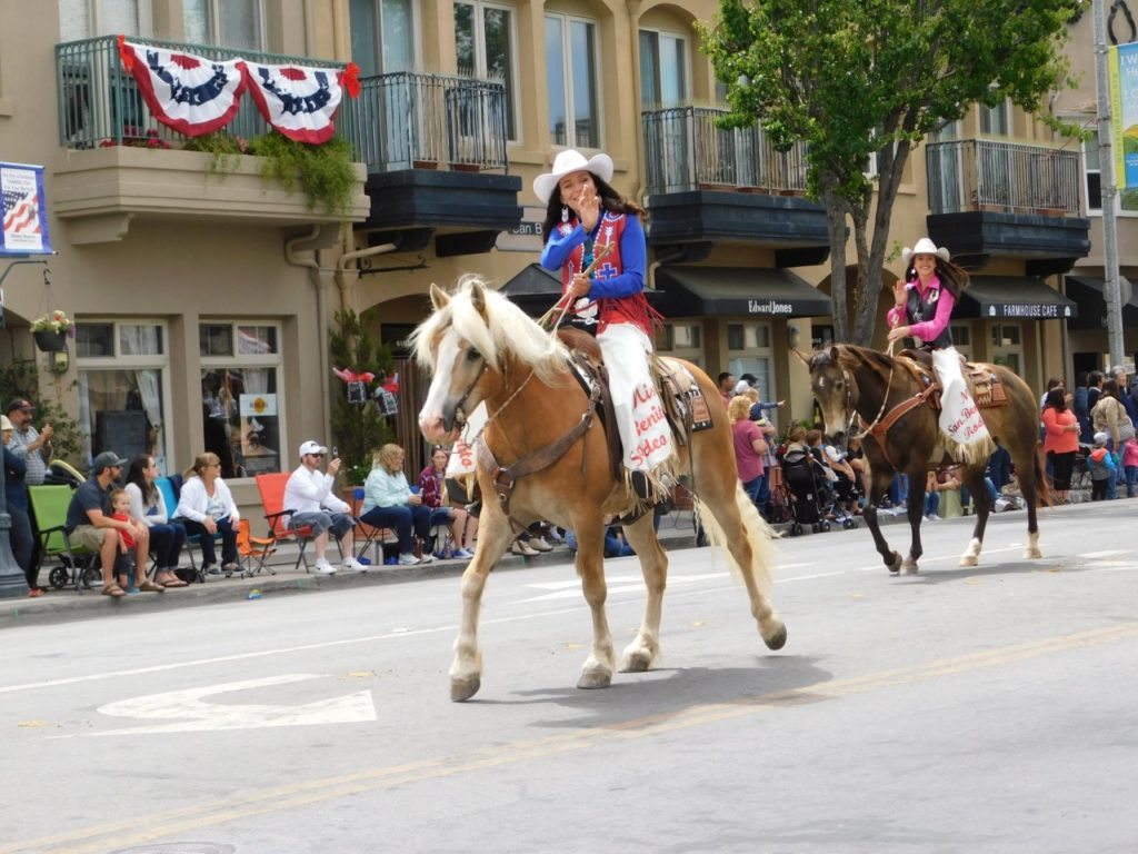 Miss San Benito Rodeo 2017 Corissa King and 2018 Queen Kelsee French, waving to the crowd at the 2018 parade in downtown Hollister. Photo by Blaire Strohn.