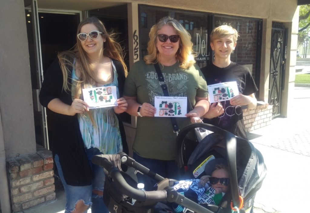 """Marni Bishop (center) and her family participated in the March 16 scavenger hunt. On top of creating a competition to see who could find the hidden items in the shortest amount of time, Bishop stated, """"I'm buying all kinds of stuff."""" Photo by Becky Bonner."""