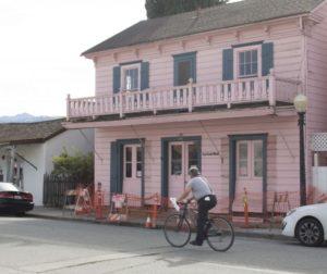 A cyclist rides past La Casa Rosa in San Juan Bautista, where the sidewalk is blocked. File photo by Noe Magaña.