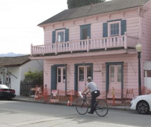A cyclist rides past La Casa Rosa in San Juan Bautista, where the sidewalk is blocked under the building's balcony. The city closed off the sidewalk in front of 107 Third Street in September 2018 after receiving a safety complaint. Photo by Noe Magaña.
