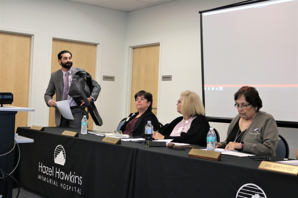 Board member Ariel Hurtado grabs his bags and leaves the April 3 Hazel Hawkins Hospital Board of Directors meeting after being told his presence could jeopardize negotiations for ACE Anesthesia Group. Hurtado is an ACE subcontractor. Photo by John Chadwell.