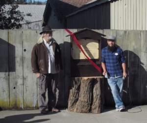John Grafton (left) and Joe Claus (right) stand next to the new kiosk for the San Juan Bautista Historic Walking Trail. Grafton came up with the idea to put the kiosk on a tree stump, while Claus crafted it. Photo by Noe Magaña.