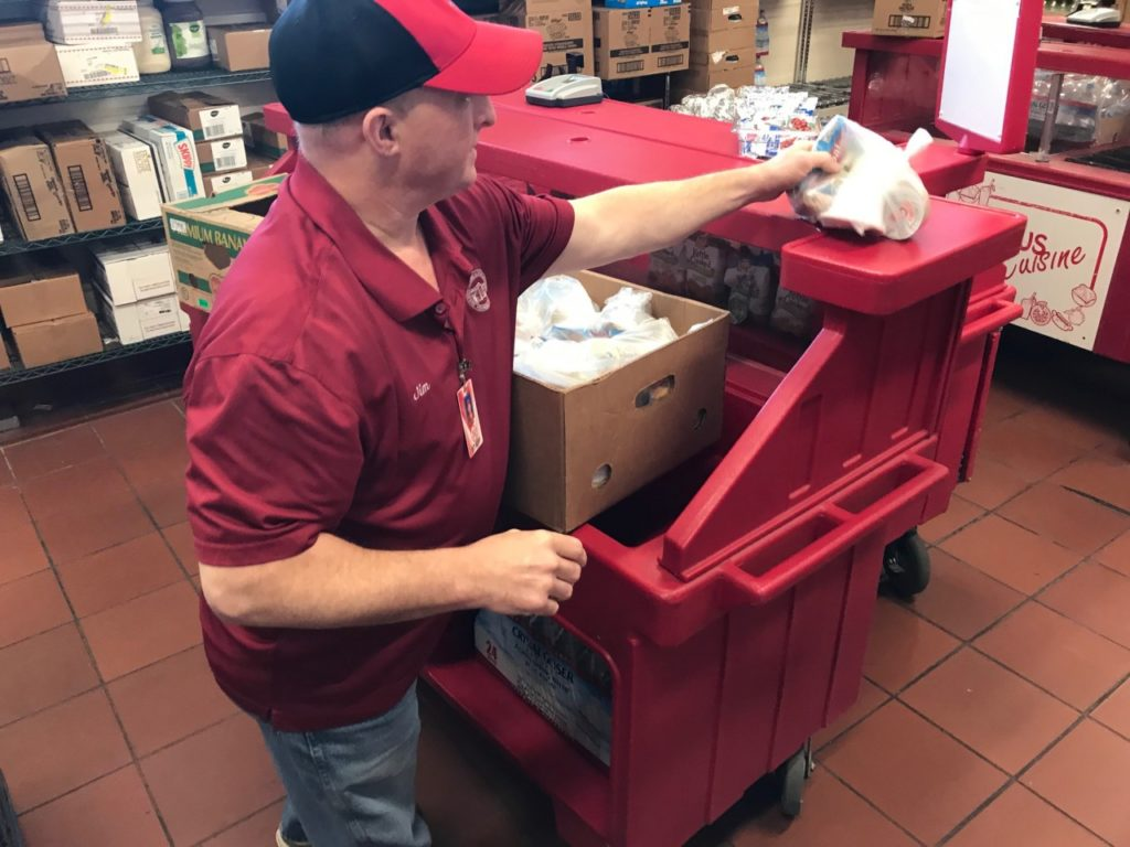 San Benito High School Food Services Manager Jim Lewis fills a box with meals that will be made available to hungry students each Friday. Photos by Adam Breen.