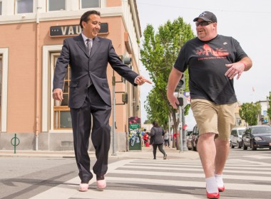 Hollister Mayor Ignacio Velazquez compliments another walker's heels as they cross the street.