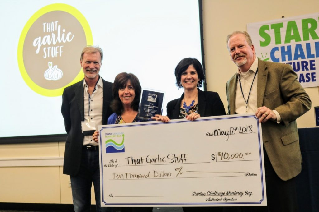 Institute for Innovation and Economic Development Executive Director Brad Barbeau, Michelle Doty and Denise Mellor of That Garlic Stuff (2018 winners of Main Street division), and judge Doug Yount at the 2018 Startup Challenge Monterey Bay. Photo courtesy of Startup Challenge Monterey Bay.
