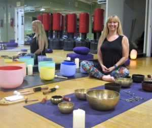 Yoga instructor Karin Larsen poses next to her sound bowls. Photo by Becky Bonner.