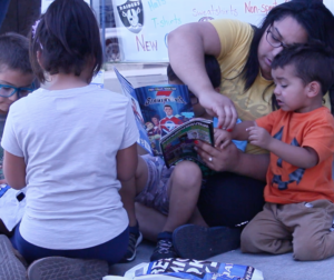 A family reads new comics outside Bill's Bullpen in Hollister on Free Comic Book Day. Photo by Noe Magaña.