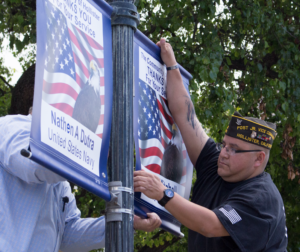 VFW member David Lopez hangs a banner for Eric Mitchell during the 2019 ceremony. Photo by Noe Magaña.