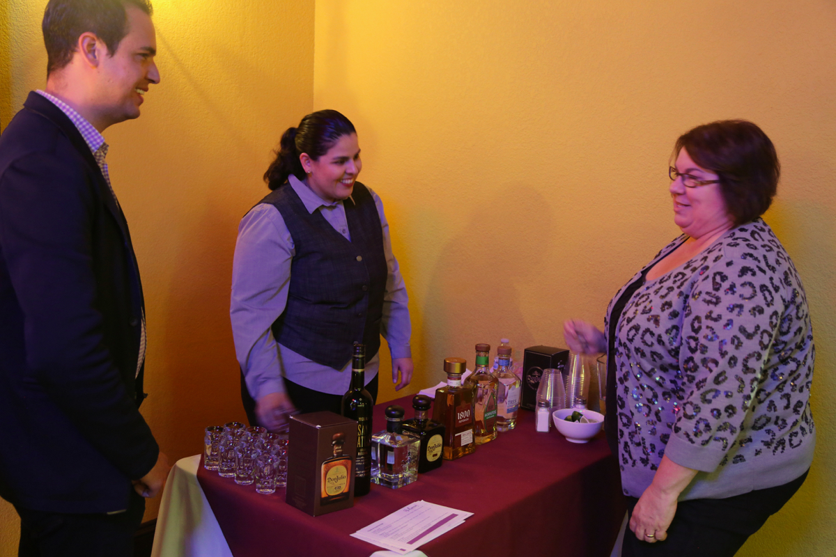 BenitoLink bookkeeper Liz Smith talking to La Catrina staff about tequila. Photo by Leslie David.