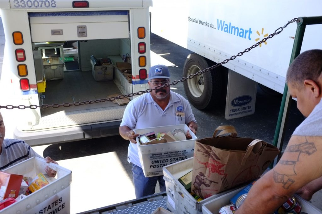 Letter carriers taking part in the annual Stamp Out Hunger food drive. Photo provided.