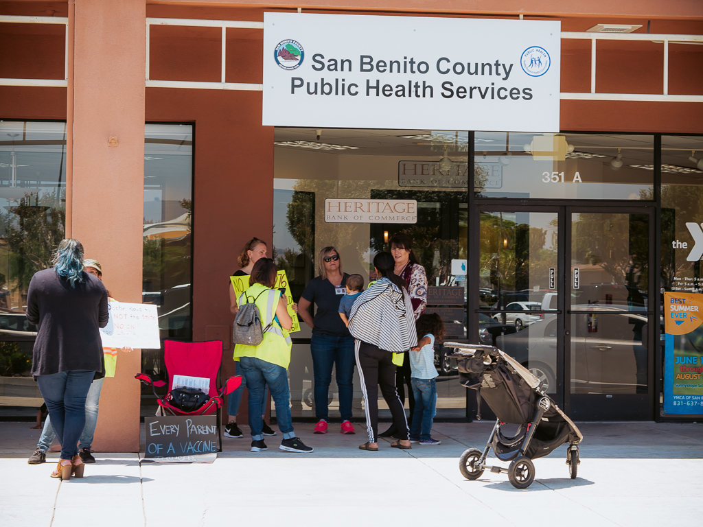 Protesters speak with county employees outside the public health offices.