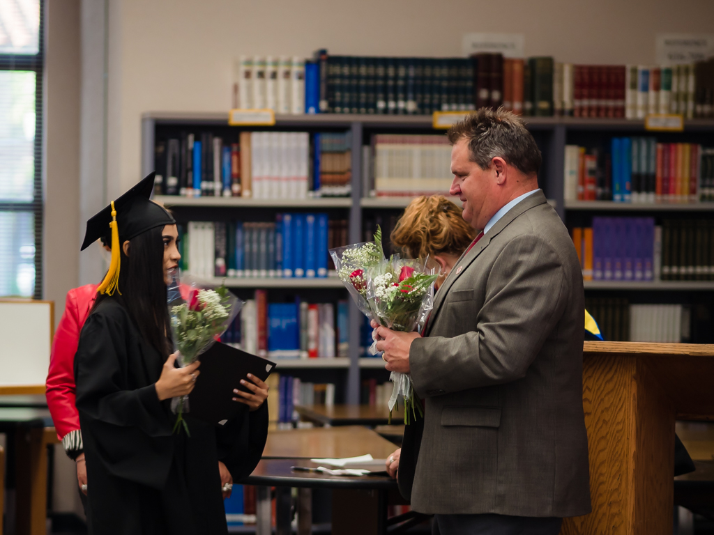John Corrigan presents Flor Orozco with flowers.