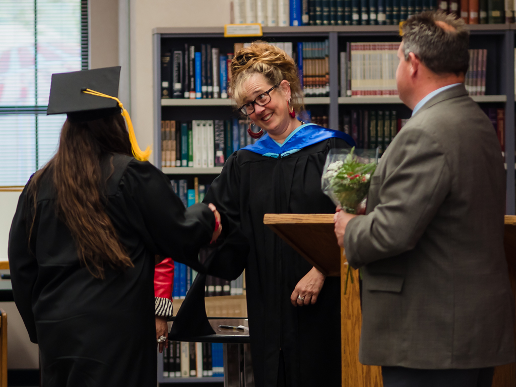Liz Pulcheon presents Nina Velez with her diploma.
