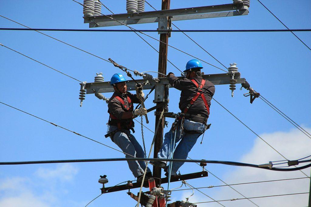 Two linemen on a telephone pole. Photo courtesy of Pixabay.