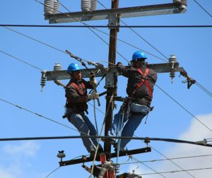 Two linemen on a telephone pole. Photo courtesy of Pixabay.