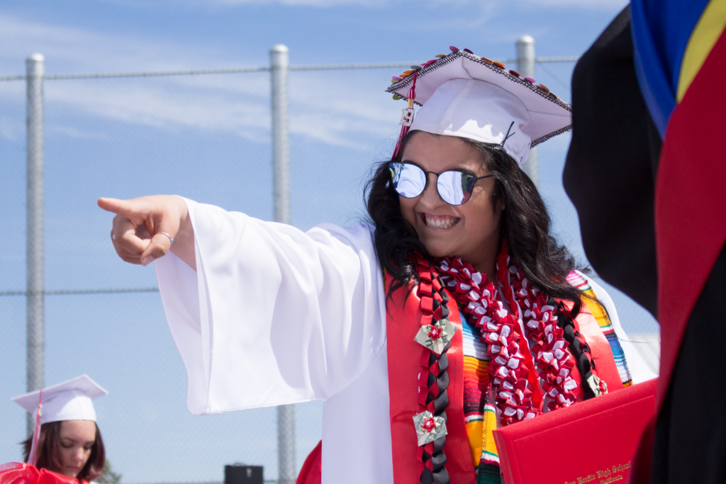 Serena Garcia points to other graduates as she walks down the stage after receiving her diploma. Photos by Noe Magaña.