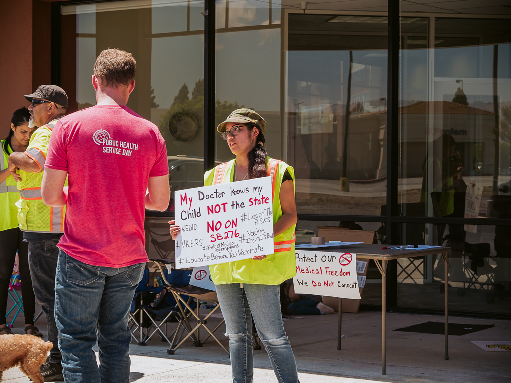 Protest organizer Deanna Escobedo holds a sign outside of the San Benito County Public Health Services office on May 31.