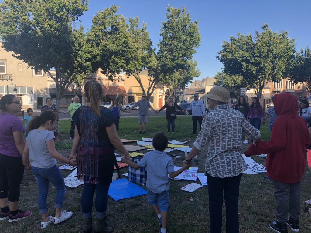 Adults and children form a circle around the signs they created for a July 26 demonstration. Photos by Melissa Melton.