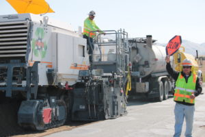 The massive grinder uses recycled asphalt from the old road to build a new road.