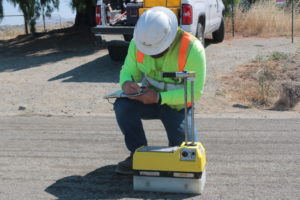 A Graniterock employee uses a density meter to check the road's density and moisture levels.
