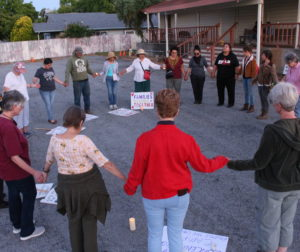 Group of demonstrators pray before the end of the vigil. Photo by Noe Magaña.