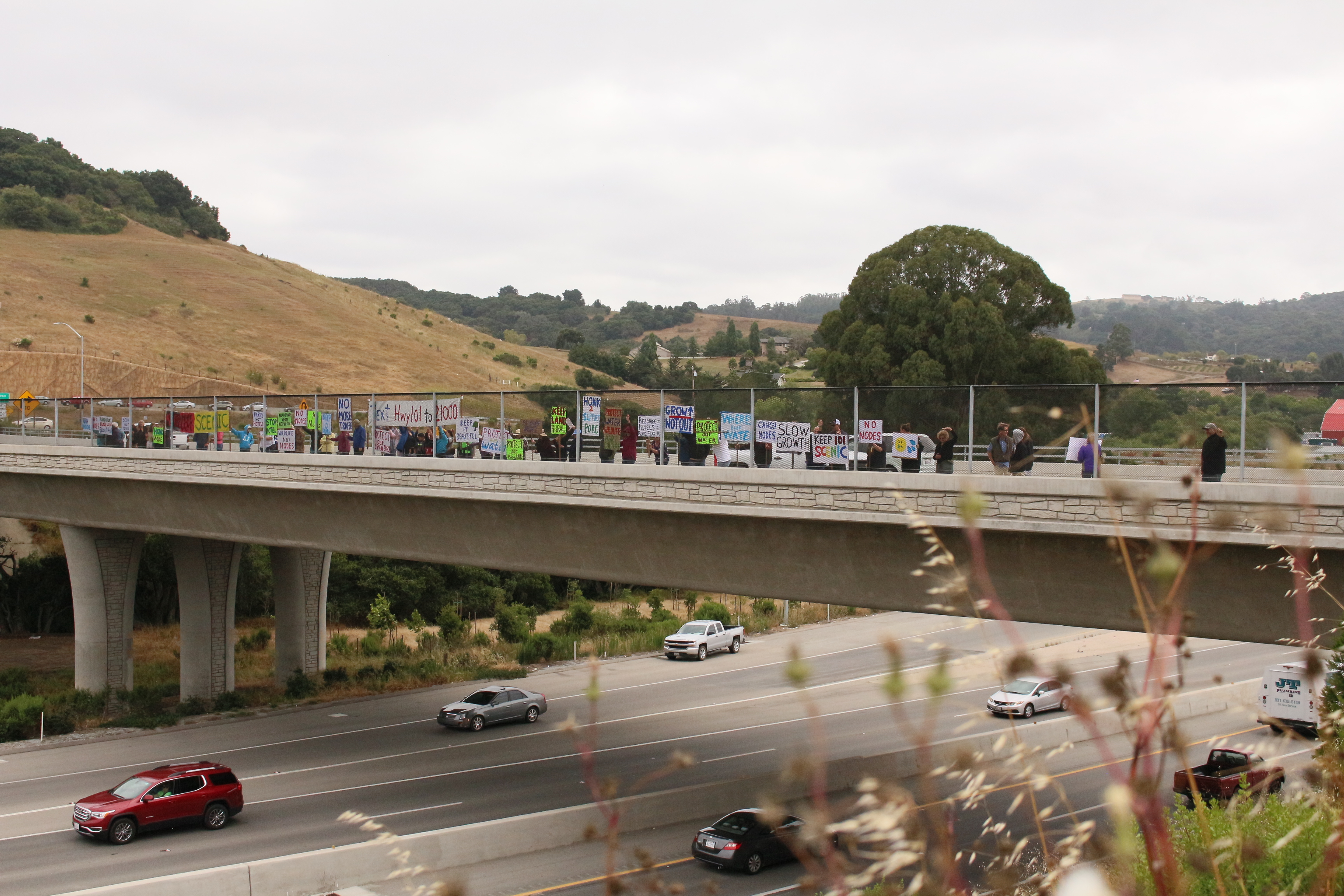 Protestors holding signs against commercial nodes on San Juan Road overpass. Photo by Noe Magaña.