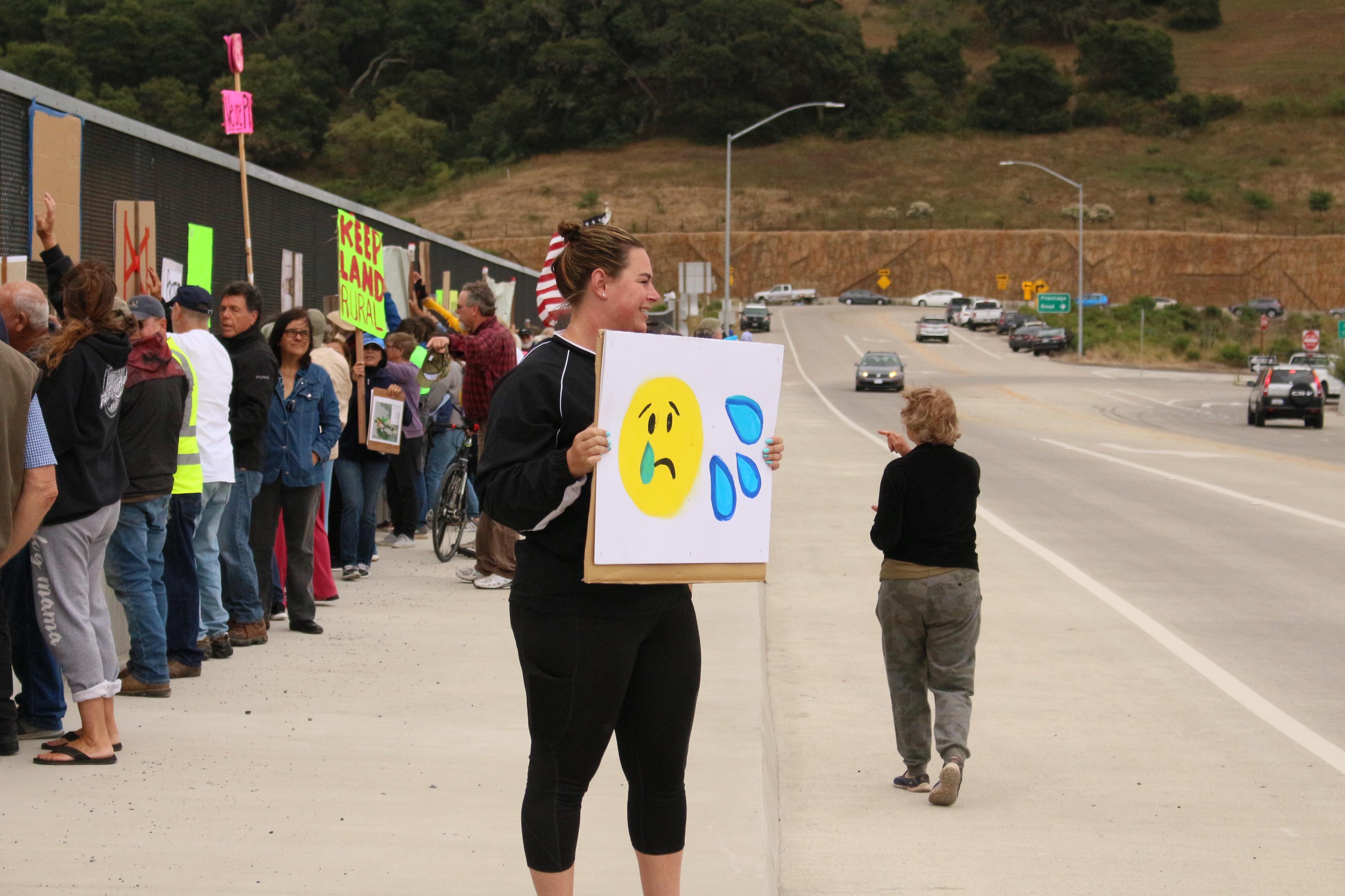 Aromas resident Liz Wyrsch holds an emoji sign toward the overpass traffic. Photo by Noe Magaña.