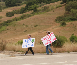 Two protestors walk toward the Highway 101 overpass during a July demonstration against the rezoning of four commercial nodes. Photo by Noe Magaña.