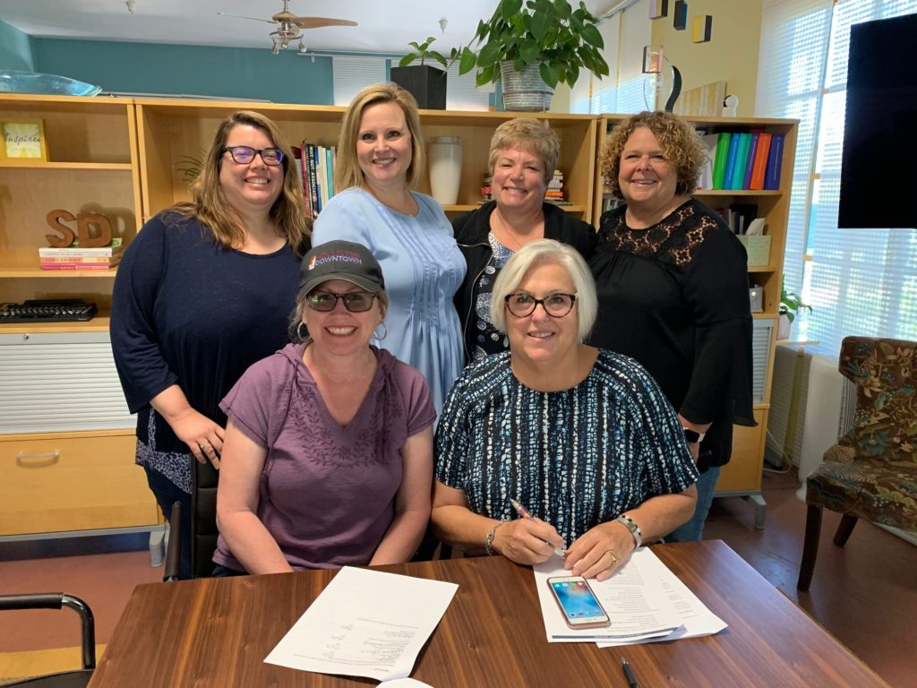 Tina Ribero, Jeana Arnold, Beth Welch, Brenda Weatherly, Jill Pagaran, and Kathy Schipper sign a contract to develop a five-year marketing plan to increase tourism in San Benito County. Photo provided by Jill Pagaran.