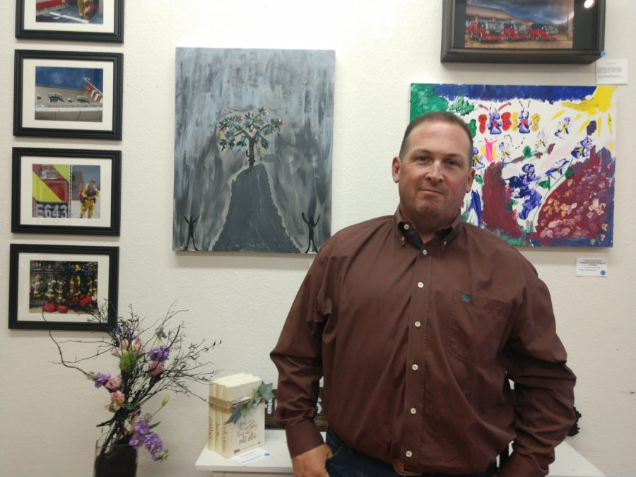 Police Chief David Westrick next to his art titled The First Crime. Photo by Carmel de Bertaut.