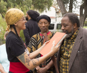Local activist Mandisa Snodey asks Minister Barry Houston to smell the aroma of a book on Africa published in 1966. Snodey received the book from biologist Roy Johnson. Photo by Noe Magaña.