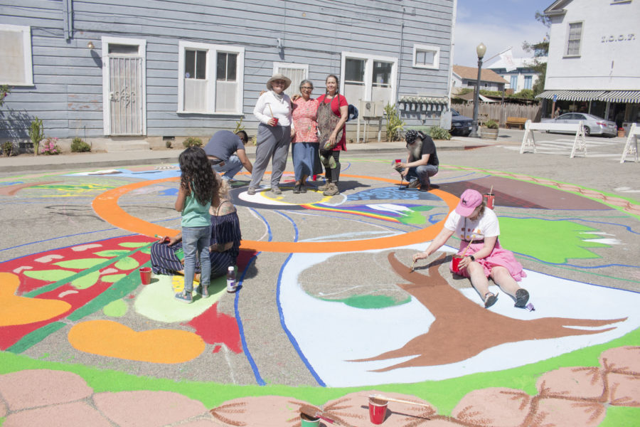 Jennifer Colby, Ramona Hill and River Sauvageau stand in the center of the mandala while others continue to paint. Photo by Noe Magaña.