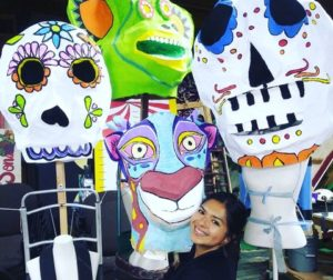 Cristal Gonzalez of El Teatro Campesino poses with masks made for the Dia de los Muertos procession. Photo provided by El Teatro Campesino.