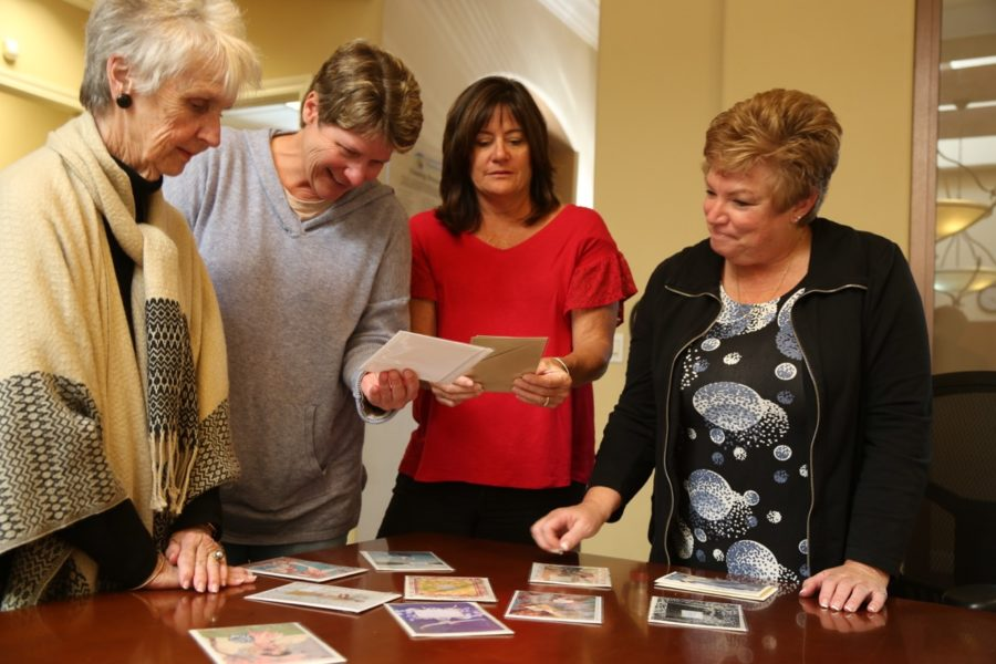 Women's Fund Committee members sort through the new card collection. Photo by Leslie David.