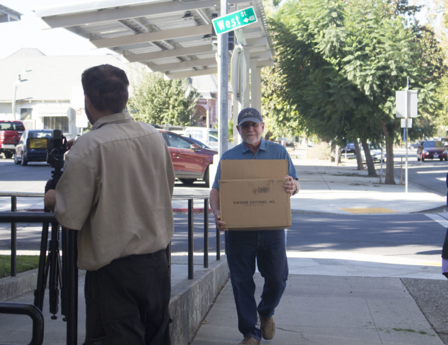 PORC treasurer Tom Karis walks to the front of San Benito County Admin building with the signed petitions.