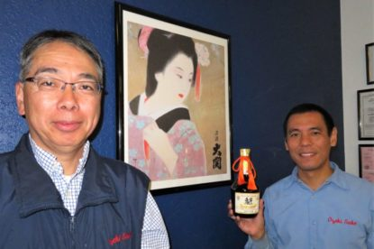 Ozeki Sake USA Inc. President Toru Ikemasu and production manager Yoji Ogawa pose with the company's 40th anniversary bottle of sake. The bottle features the city of Hollister's logo. Photos by Becky Bonner.