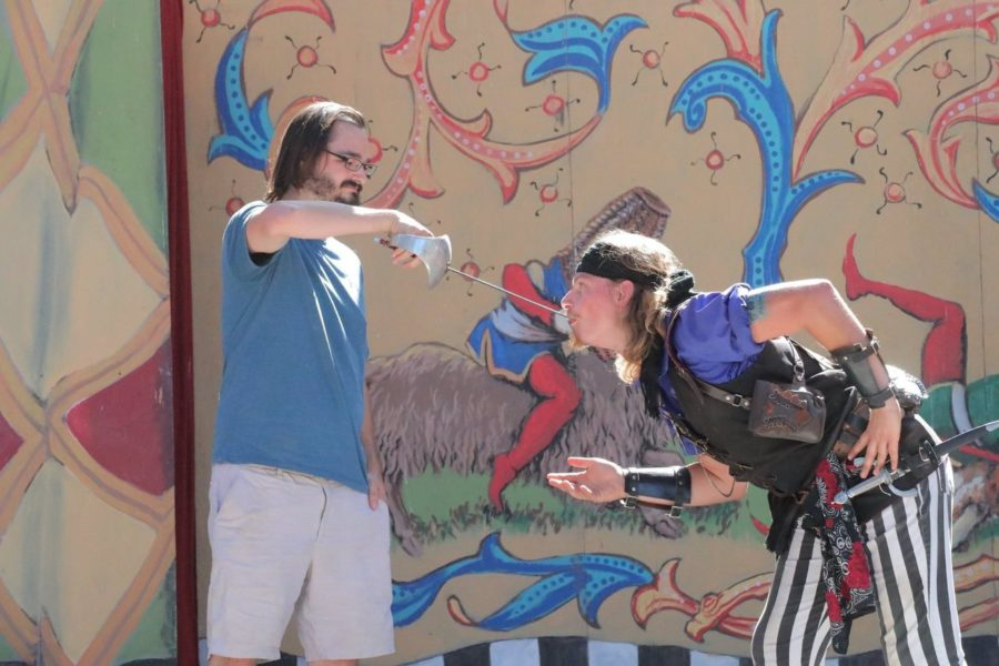 A volunteer pulls a sword from Cydeshow Cy's throat.