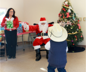 Santa greets an enthusiastic child. Photo provided by Community Services and Workforce Development.