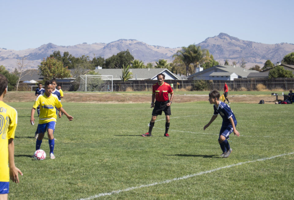 Referee Alvaro Quezada keeps close watch during a boys soccer game. Photos by Noe Magaña.