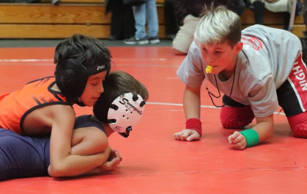 11-year-old referee Stephen Seymour judges a wrestling match. Photos by Robert Eliason.