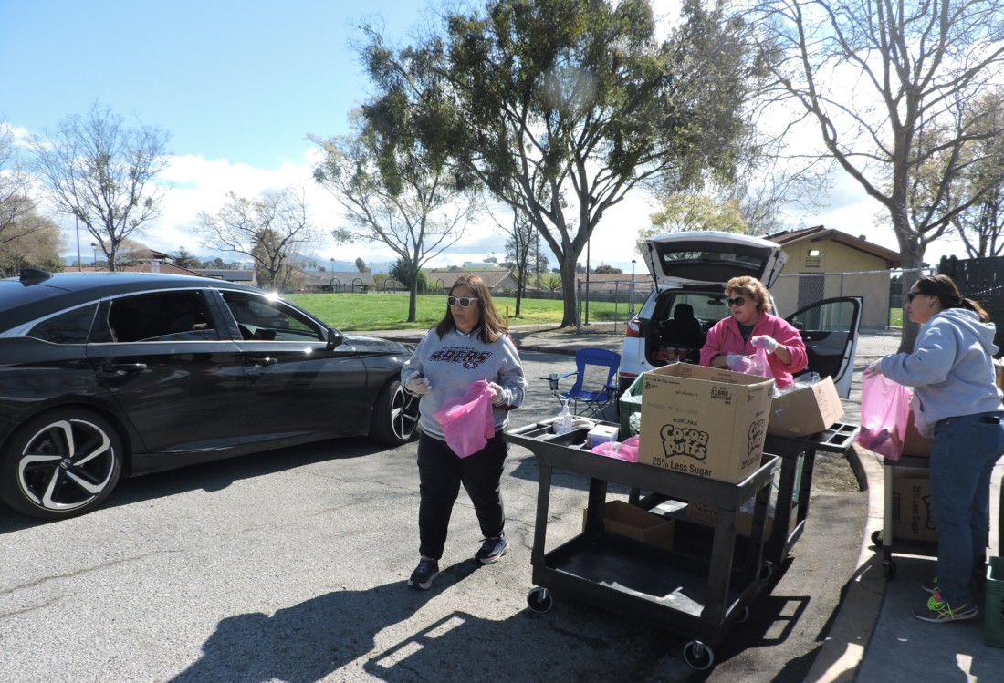 Nutrition workers Eva Hernandez, Karen Kulpa and Dora Sanchez distribute food to families as they drive up. Photo by Patty Lopez Day.