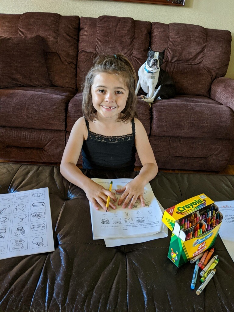 Adeline works on her review packet with her dog watching over her. Photo provided.