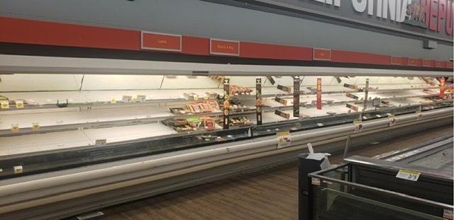A nearly empty meat fridge.