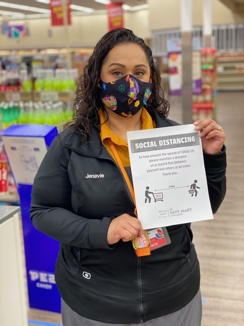 Jenavie holds a social distancing flyer posted around the store. She wears a mask she brought from home, along with a lanyard with hand sanitizer.