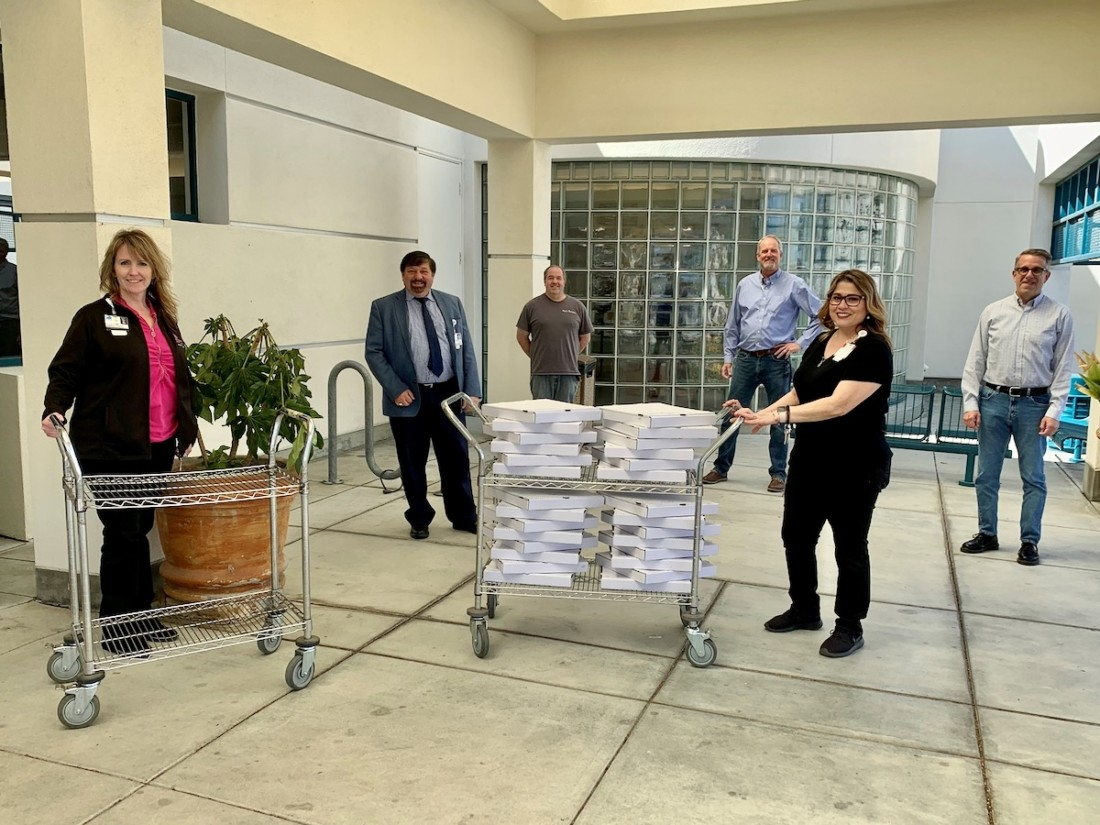 Just a few of the pizzas delivered to Hazel Hawkins Memorial Hospital staff by Graniterock and Granite Construction. Don Barrett with Graniterock (center) in blue. Hospital staff names were not provided by publication. Photo provided.