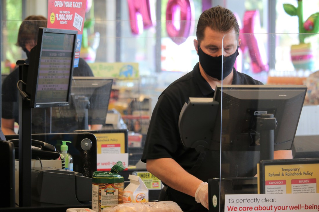 Cashier wearing a face mask. Photo by John Chadwell.