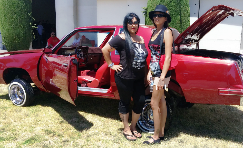 Sandra Casarez and Amanda Sosa pose in front of a lowrider in San Jose. Photo provided.