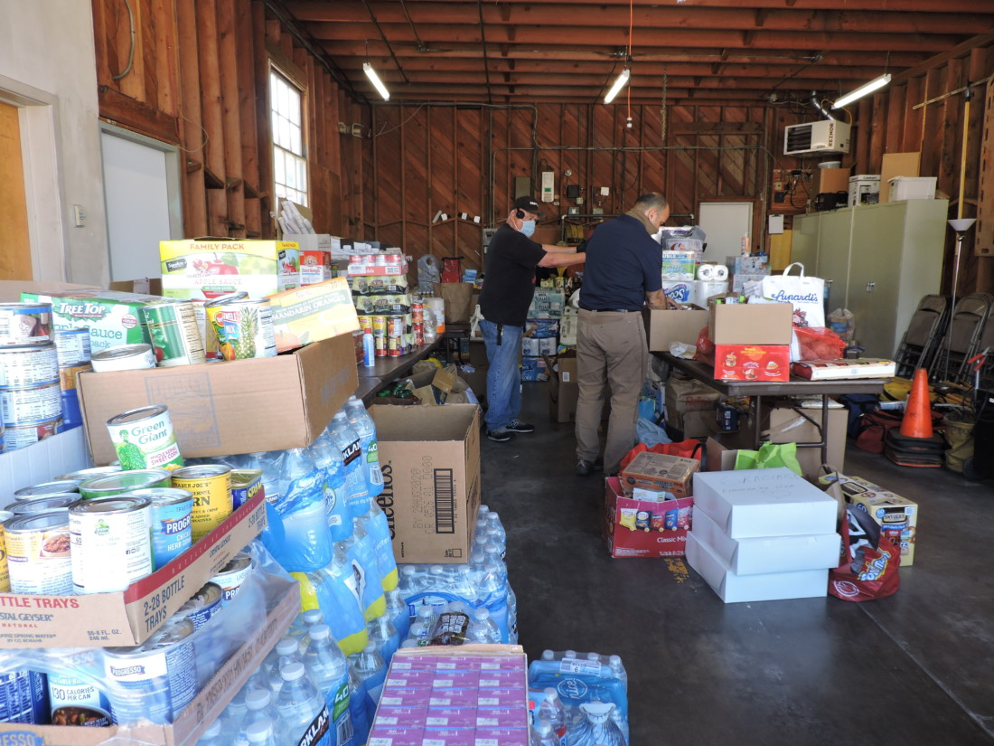 Phil Esparza and Congressman Jimmy Panetta sort supplies collected during the farmworker relief drive on May 23. Photo by Patty Lopez Day.