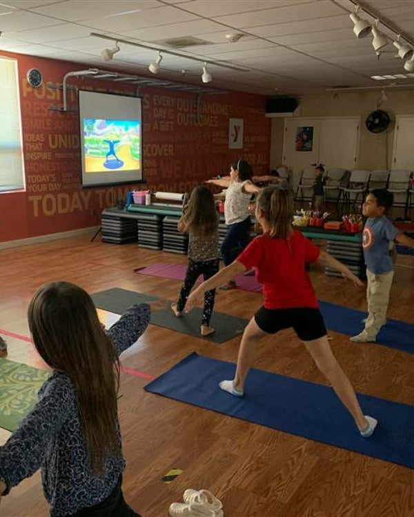 """YMCA camp participants during their virtual yoga session. """"The YMCA camp program has allowed the kids the freedom to be kids and stay active from morning to afternoon with classwork and activities such as virtual yoga!"""